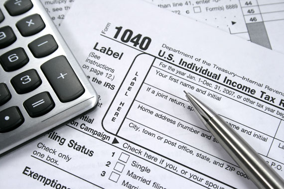 Close up of tax forms, a calculator and a pen.