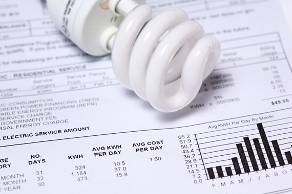 Close up of a compact fluorescent lightbulb on top of a paper Utilities bill